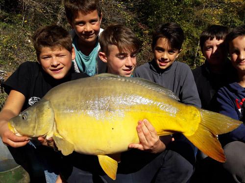 Groupe de jeunes pêcheurs avec une carpe miroir